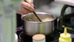 The chef mixes barley porridge with spices in a saucepan on the stove. Stock Footage