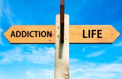 ADDICTION versus LIFE messages written on opposite arrows. - stock photo