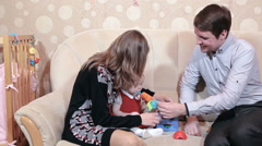 Pretty baby girl playing educational toys with adult parents. Three people  Stock Footage