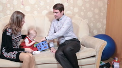 Little baby playing educational toys while sitting sofa with father and mother - stock footage