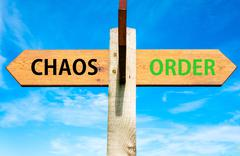 Chaos versus Order messages written on opposite arrows. - stock photo