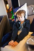 Child is relaxing and watching a film in an aircraft in business class Stock Photos
