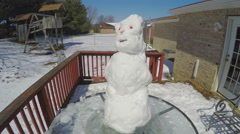 4K snowman melting and falling over close to real time Stock Footage