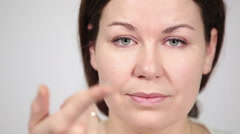 Caucasian woman holding extended wear contact lens on finger, camera focusing Stock Footage