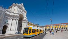 Modern tram and a tourist bus pass by the Augusta Street Arch in Lisbon Stock Footage