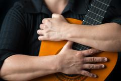 Musician hands embracing a classic acoustic guitar Stock Photos