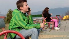 Teenagers On Separated Benches In Park With Mobile Phone, Boy In Focus, - stock footage