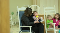 Nursery Worker Sitting in Rocking Chair and Playing with Baby's Feet Stock Footage