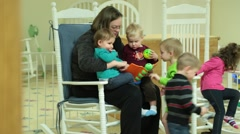 Stock Video Footage of Nursery Worker Seated in Rocking Chair and Caring For Children