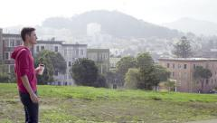 Man Drinks Coffee, Checks His Phone, Walks Through Alamo Square In San Francisco Stock Footage