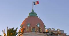 La Nice south France Nizza french rivera hotel Le Negresco flag waving windy 4K Stock Footage