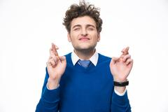 Young man with crossed fingers over white background Stock Photos
