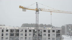 Crane lift block house part and builders work in heavy blizzard Stock Footage