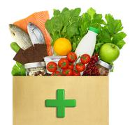 Paper bag with medical green cross filled with healthy foods - stock photo