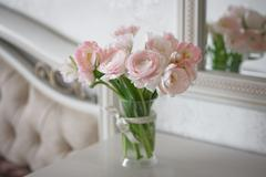 Bouquet of delicate ranunculus and tulips in interior Stock Photos