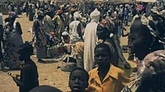 Senegal 1985: people walking in an outdoor market Stock Footage