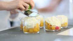 Cook rubbing lemon zest with grater over dessert Stock Footage