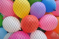 some toy balloons in a net - stock photo