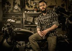 Rider and his vintage style cafe-racer motorcycle in customs garage Stock Photos