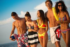 Group of multi ethnic friends walking on a beach Stock Photos