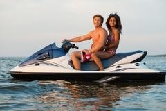 Multi ethnic couple sitting on a jet ski Stock Photos