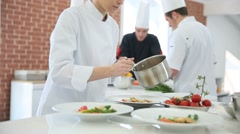 Young woman in cooking class pouring sauce on plate Stock Footage