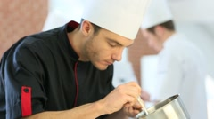 Chef in restaurant kitchen preparing dish - stock footage