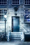 Night scene with a door and a light poll - stock photo