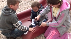 Boy and girl put a shoe on baby Stock Footage