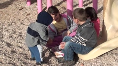 Child in hood shares pebbles with other children Stock Footage