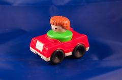 Red toy car driven by a dark toy driver on blue background Stock Photos