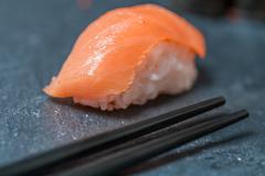 salmon sushi with chopsticks - stock photo