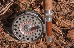 An old fly reel mounted on a flyrod - stock photo