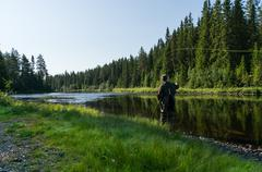 Flyfisherman casting in the river - stock photo