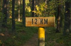 A wooden sign indicating the distance twelve kilometers Stock Photos