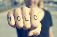 Closeup of a young man with the word yolo, for you only live once, tattooed i Stock Photos
