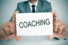 Man with a signboard with the word coaching Stock Photos