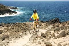 boy riding his mountainbike offroads and doing tricks - stock photo