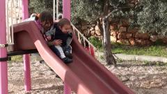 Elder children and toddler on slide Stock Footage