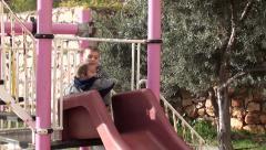 Elder boy tries to make a toddler slide Stock Footage