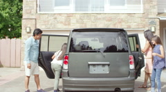 A family of four gets into a car which is sitting in the driveway of their house - stock footage