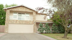 Shot of a large house with a driveway, in the suburbs, with rack focus  Stock Footage