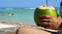 Woman holding fresh coconut on the beach - stock footage