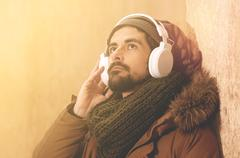 Stock Photo of a young man listens to music in an urban image of modern life warm tones styl
