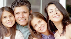 A hispanic family smile at the camera while on a bench outside of their house - stock footage