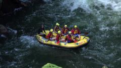 Tourists white water rafting wave to camera, Rotorua, New Zealand Stock Footage