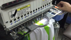Computerized embroidery machine, working on lacing Thai text on T-shirt Stock Footage