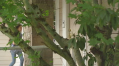 Two young girls run up and open the front door to their house Stock Footage