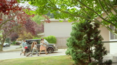 A family returns home from a picnic and walks into their house Stock Footage