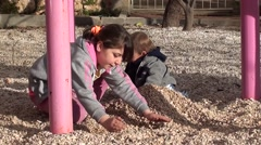 Girl and toddler are playing with heap of stones 4 Stock Footage